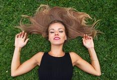 Jonge onbezorgde vrouw die in gras en het dromen liggen Stock Fotografie