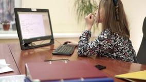 Jonge onderneemster bij haar bureau die aan de computer op haar kantoor werken stock footage