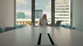 Jonge onderneemster in conferentieruimte met documenten Elegante blonde vrouwenzitting bij lange lijst in moderne zaal van bureau stock video