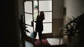 Jonge onderneemster die aan de flat met koffer binnengaan Het wijfje opent de deur en het uitgaan op treden Royalty-vrije Stock Foto's