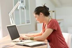 Jonge onderneemster die aan laptop thuis werken royalty-vrije stock foto