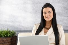 Jonge onderneemster die bij laptop het glimlachen werkt Stock Foto's