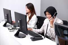 Jonge onderneemster die de telefoon beantwoorden terwijl het werken van het gebruiken stock foto