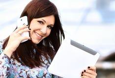 Jonge onderneemster die digitale tablet en mobiele telefoon met behulp van royalty-vrije stock fotografie