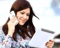 Jonge onderneemster die digitale tablet en mobiele telefoon spreken stock fotografie