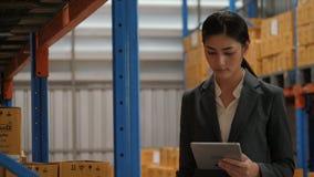 Jonge onderneemster die digitale tablet gebruiken die voorraad in industrieel pakhuis controleren stock footage