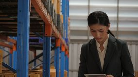 Jonge onderneemster die digitale tablet gebruiken die voorraad in industrieel pakhuis controleren stock videobeelden