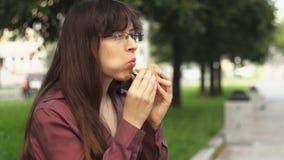 Jonge onderneemster die een kleine hamburgerzitting op een bank in het park eten stock videobeelden