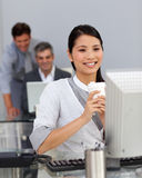Jonge Onderneemster die een koffie drinkt bij haar bureau Stock Foto's