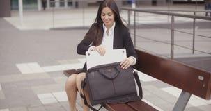 Jonge onderneemster die haar laptop plaatsen in een zak stock footage