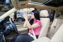 Jonge onderneemster die make-up in een auto doen stock afbeeldingen
