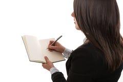 Jonge onderneemster die in notitieboekje schrijft Stock Afbeelding