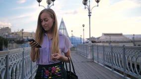 Jonge onderneemster die op brug met telefoon lopen stock videobeelden