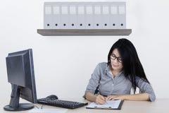 Jonge onderneemster die op het klembord schrijven stock foto's