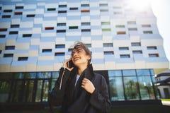 Jonge onderneemster die op mobiele telefoon tijdens openluchtkoffiepauze, dichtbij de bureaubouw spreken Communicatie concept stock fotografie