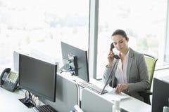 Jonge onderneemster die op telefoon in bureau spreken stock afbeeldingen