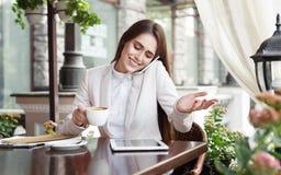 Jonge onderneemster die op telefoon en het drinken koffie in openlucht spreken Royalty-vrije Stock Foto