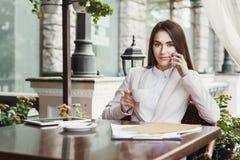 Jonge onderneemster die op telefoon en het drinken koffie in openlucht spreken Stock Afbeelding