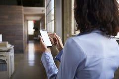 Jonge onderneemster die smartphone in bureau gebruiken, achtermening stock afbeelding