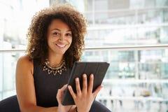 Jonge onderneemster die tabletcomputer in modern binnenland met behulp van Royalty-vrije Stock Foto