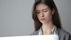 Jonge onderneemster die via computer, grijze achtergrond werken stock video