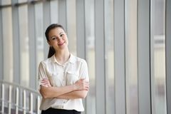 Jonge onderneemster die zich door venster in bureau bevinden Mooi jong vrouwelijk model in helder bureau royalty-vrije stock foto