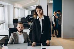 Jonge onderneemster en zakenman die in bureau samenwerken en de camera bekijken stock foto