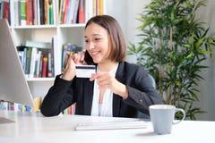 Jonge onderneemster met creditcardzitting achter het bureau stock afbeelding