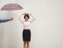 Jonge onderneemster met haar hand boven hoofd, medewerker die haar paraplu geven Royalty-vrije Stock Afbeeldingen