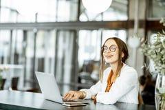 Jonge onderneemster met laptop in de bar of het bureau royalty-vrije stock foto's