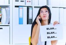Jonge onderneemster tijdens nutteloos gesprek met de cliënt of de werkgever Efficiënt communicatie concept royalty-vrije stock afbeelding