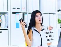 Jonge onderneemster tijdens nutteloos gesprek met de cliënt of de werkgever Efficiënt communicatie concept stock foto