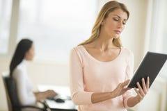 Jonge Onderneemster Using Digital Tablet op Kantoor stock foto's