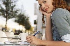 Jonge Onderneemster Writing On Paper bij Openluchtkoffie stock afbeeldingen