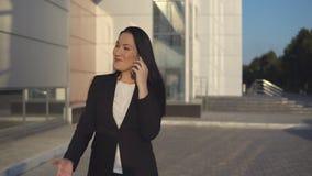 Jonge onderneemster in zwart kostuum die op smartphone tegen de achtergrond van bureaucentrum spreken op zonnige dag stock video