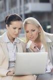 Jonge onderneemsters die aan laptop samenwerken terwijl in openlucht het zitten Stock Fotografie