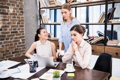 Jonge onderneemsters die bij bureau met laptop en het bespreken samenwerken Stock Afbeelding