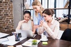 Jonge onderneemsters die bij bureau met laptop en het bespreken samenwerken Stock Afbeeldingen
