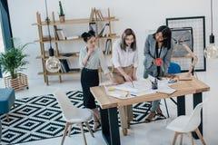 Jonge onderneemsters die met blauwdruk en het drinken koffie in modern bureau werken Royalty-vrije Stock Afbeeldingen