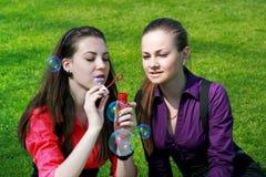 Jonge onderneemsters die zeepbels blazen Stock Afbeeldingen