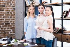 Jonge onderneemsters die zich bij bureau tijdens koffiepauze verenigen Royalty-vrije Stock Afbeelding