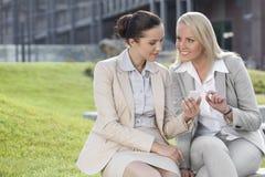 Jonge onderneemsters met mobiele telefoonzitting tegen de bureaubouw Royalty-vrije Stock Foto