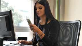 Jonge onderneemsterzitting bij bureau in bureau bezig op telefoon royalty-vrije stock fotografie