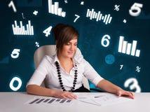Jonge onderneemsterzitting bij bureau met diagrammen en statistieken Stock Fotografie