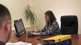 Jonge onderneemsterzitting bij het bureau in haar bureau die aan de computer werken stock video