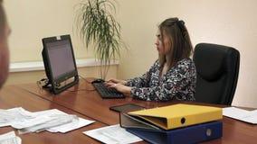 Jonge onderneemsterzitting bij het bureau in haar bureau die documenten van een werknemer nemen stock footage