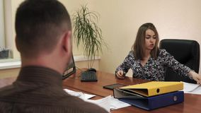 Jonge onderneemsterzitting bij het bureau in haar bureau die taken geven aan een werknemer stock video