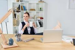 Jonge onderneemsterzitting in bureau bij haar bureau, holding een kop Stock Foto