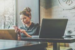 Jonge onderneemsterzitting in koffie bij lijst dichtbij venster en het gebruiken van smartphone Op bureau is laptop en kop van ko Royalty-vrije Stock Afbeeldingen