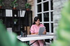 Jonge onderneemsterzitting met haar tablet in het bureau stock foto